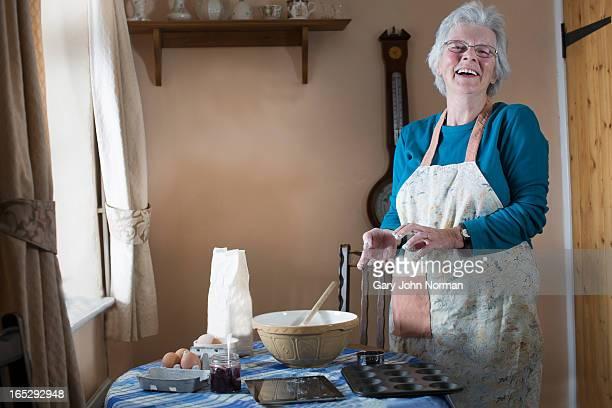 senior woman baking at table ,laughing