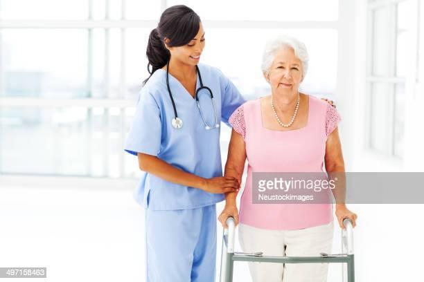 Donna anziana è assistita da infermiera con Deambulatore