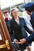 Senior woman being greeted at door by hotel doorman