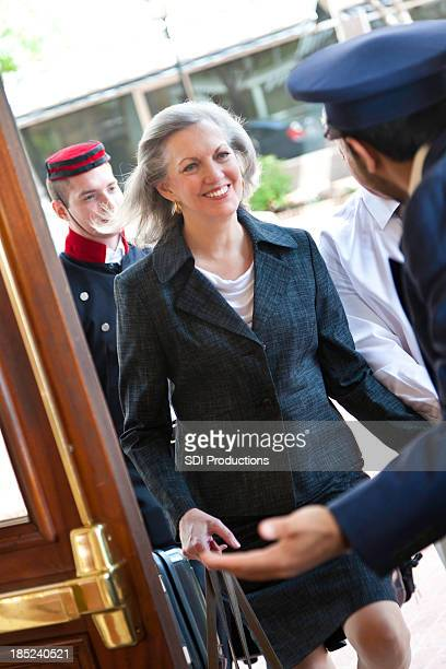 Senior woman being greeted at door by hotel doorman