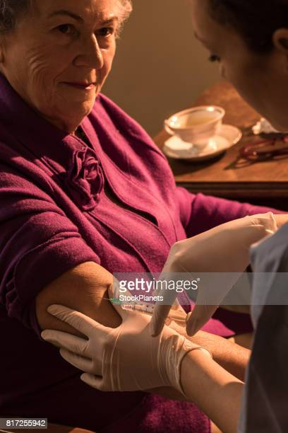 Senior woman being vaccinated at home by home caregiver.