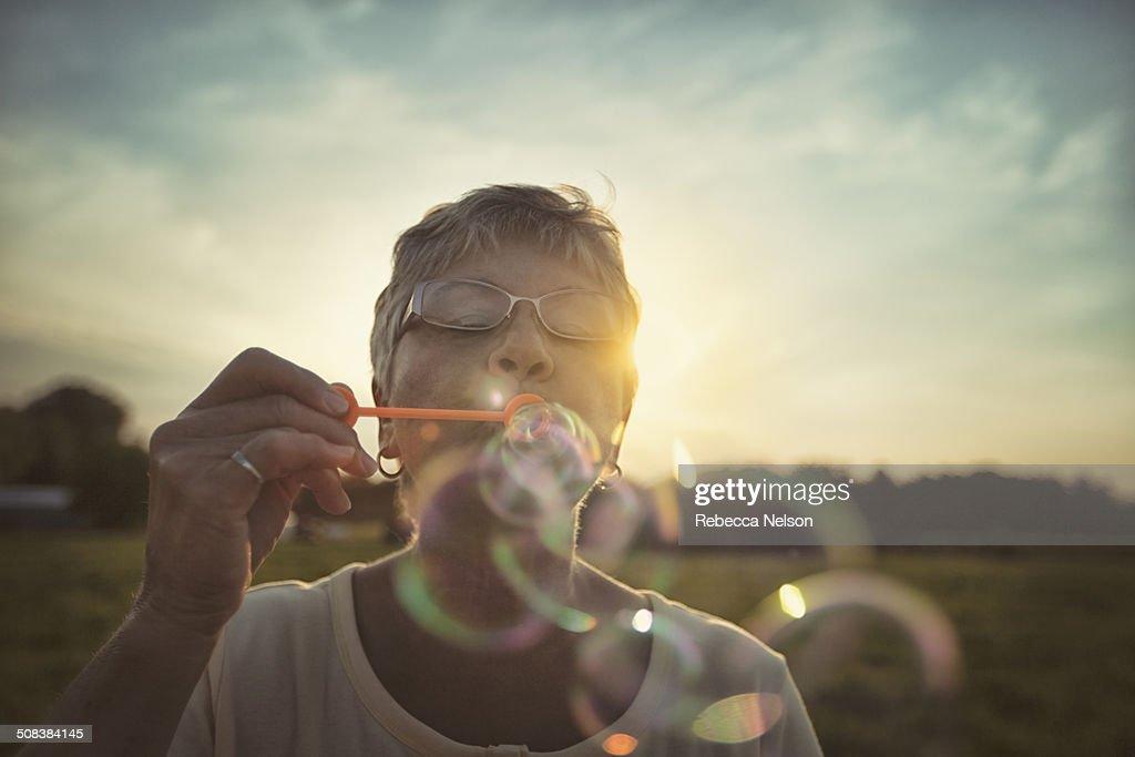 Senior woman blowing bubbles