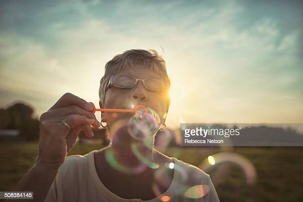 Senior woman blowing bubbles