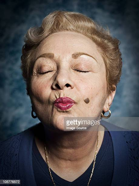 Senior woman blowing kiss, eyes closed
