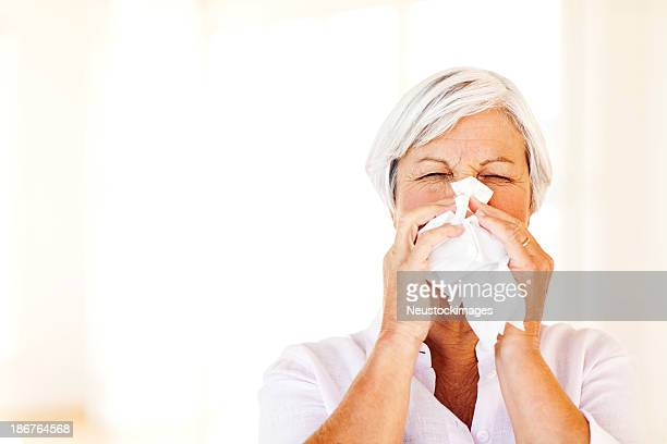 Senior Woman Blowing Nose With Tissue At Home