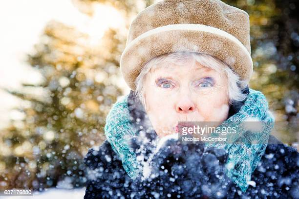 Senior woman blowing snow  to camera sunset forest Canada