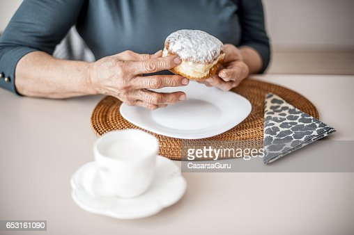 Senior Woman Break The Rules By Eating Donut : Stockfoto