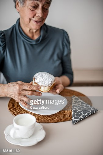Senior Woman Break The Rules By Eating Donut : Stock Photo