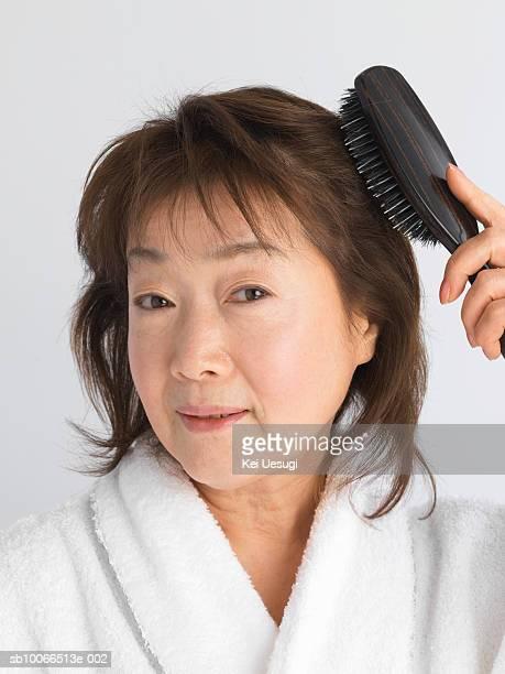 Senior woman brushing hair, close-up
