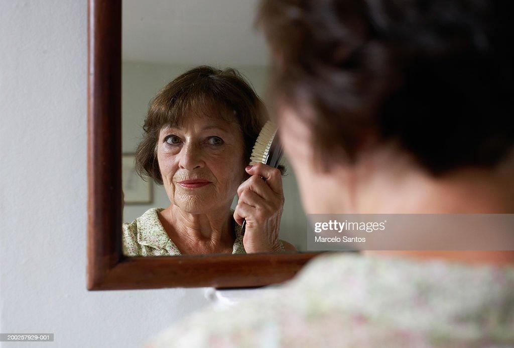 Senior woman brushing hair in mirror (focus on reflection)