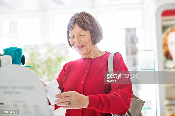 Senior woman buying medicine at pharmacy