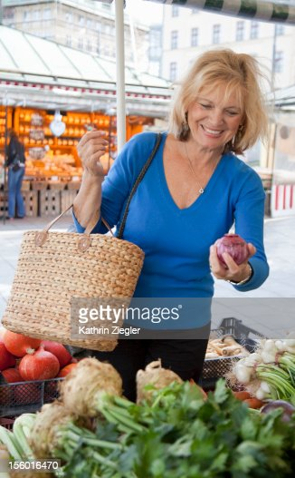 senior woman buying vegetables at the market : Bildbanksbilder