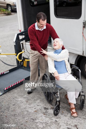 Senior woman by minibus with wheelchair lift