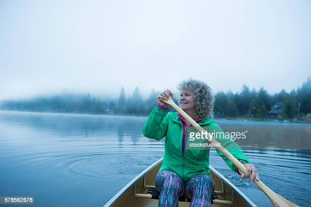 Senior woman canoeing on a prisitine lake