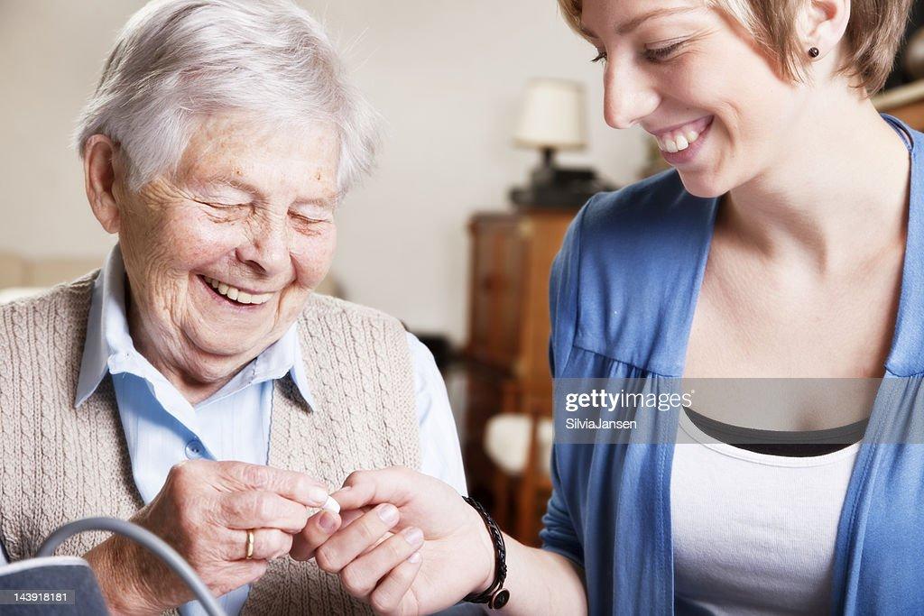 senior woman, caregiver and medicine