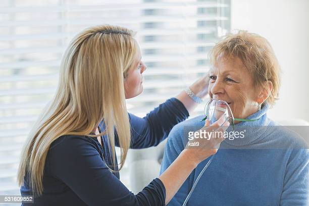 Senior woman, caregiver helping with oxygen mask