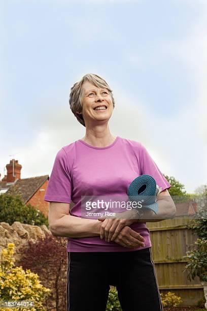 Senior woman carrying yoga mat