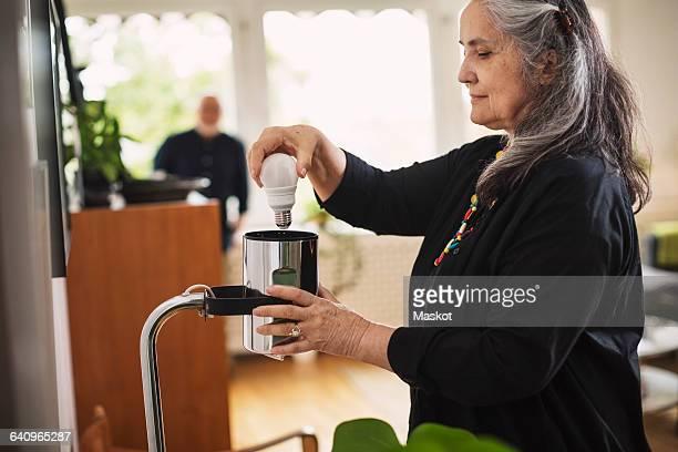 Senior woman changing bulb at home