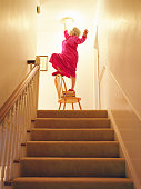 Senior woman changing light bulb above staircase, balancing on chair