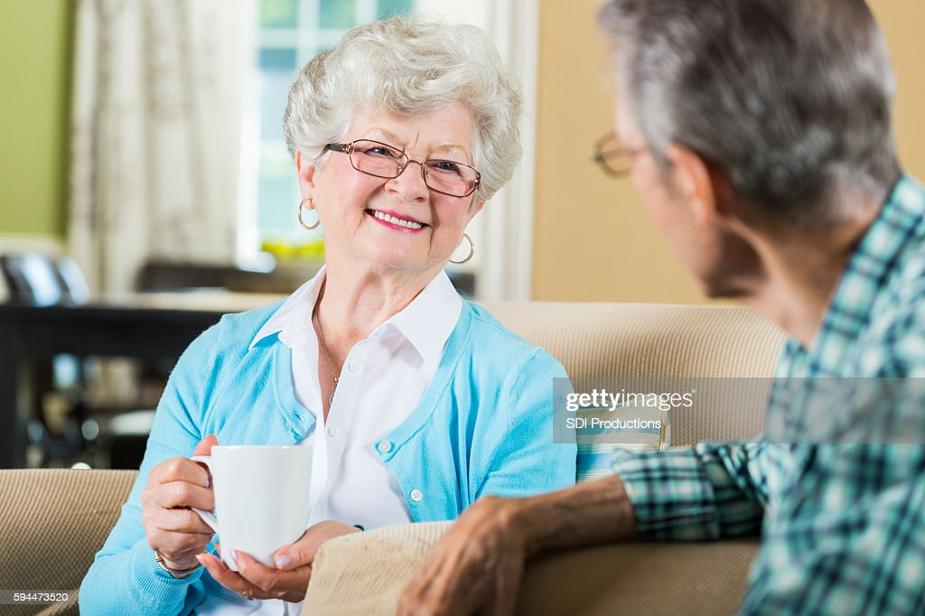 Senior woman chats with husband in living room