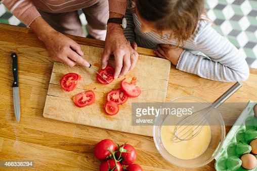 Senior woman chopping tomatoes with her granddaughter in kitchen