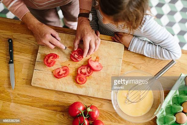 Idosa a cortar tomates com sua Neta na cozinha