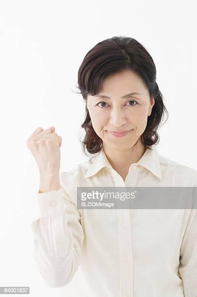 Senior woman clenching fist, studio shot