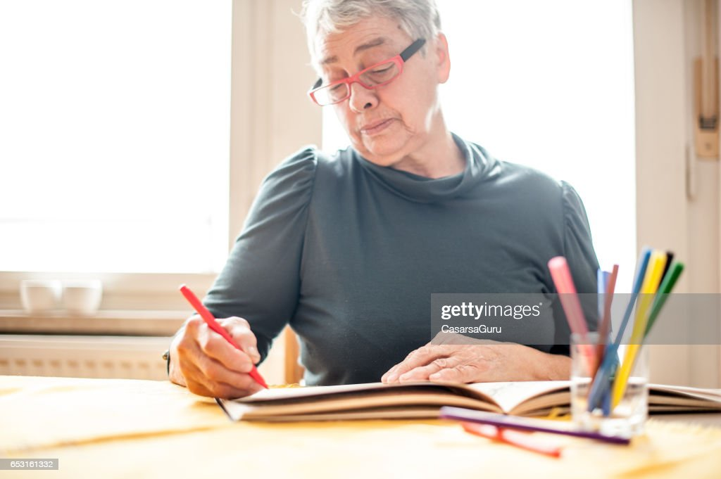 Senior Woman Coloring An Adult Coloring Book : Photo