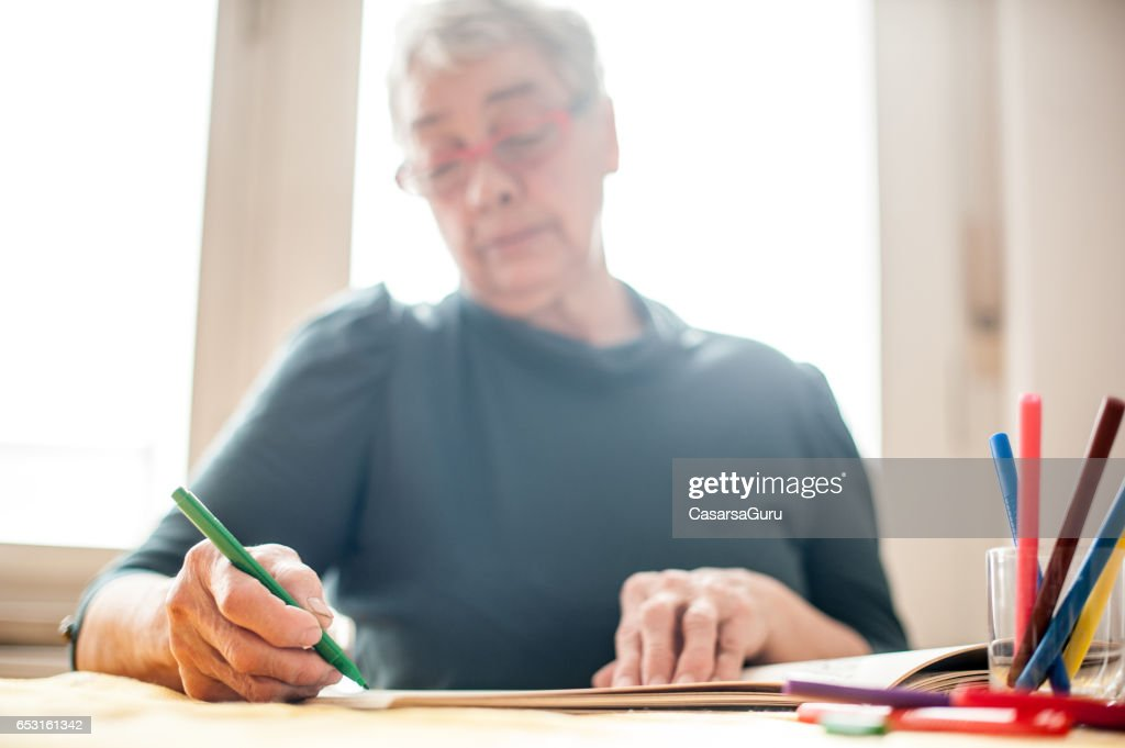 Senior Woman Coloring An Adult Coloring Book : Foto stock