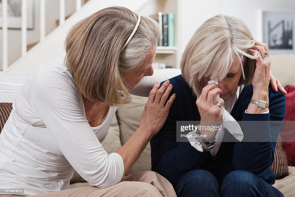 Senior woman comforting crying friend
