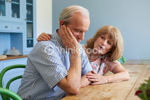 Senior Woman Comforting Man With Depression At Home : Stock Photo