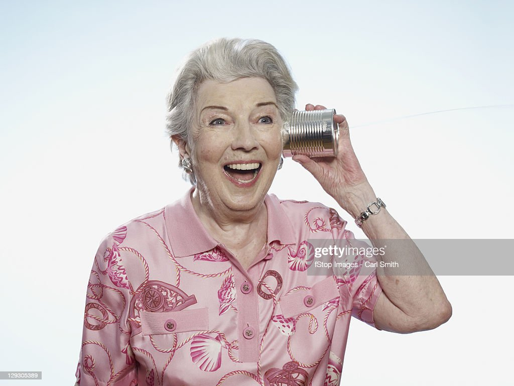 Senior woman comically listens to tin can phone
