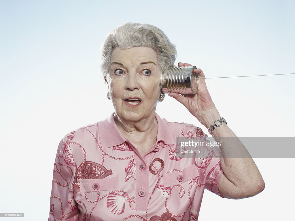 Senior woman comically strains to listen as she holds a tin can phone to her head