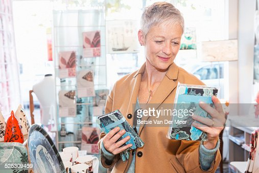 senior woman compares products in shop.