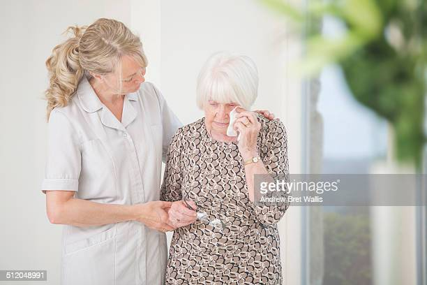 Senior woman consoled by carer