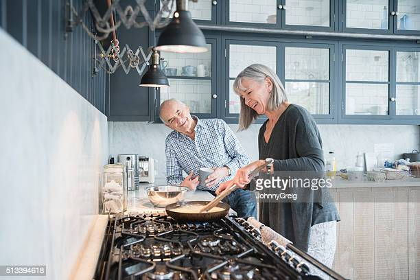 Senior woman cooking dinner talking to her husband