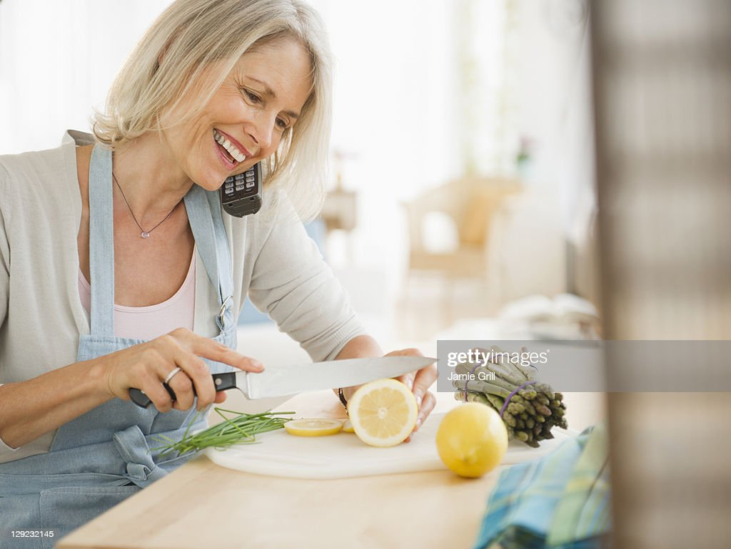 Senior woman cooking while talking on phone : Stock Photo