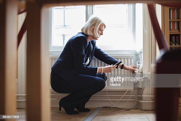 Senior woman crouching while charging mobile phone by radiator with furniture in foreground at library