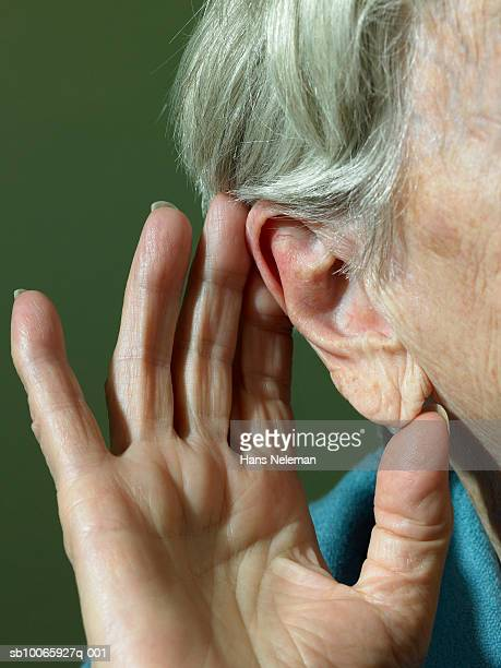 Senior woman cupping hand to ear, close-up