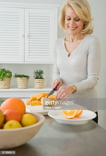 Senior woman cutting oranges