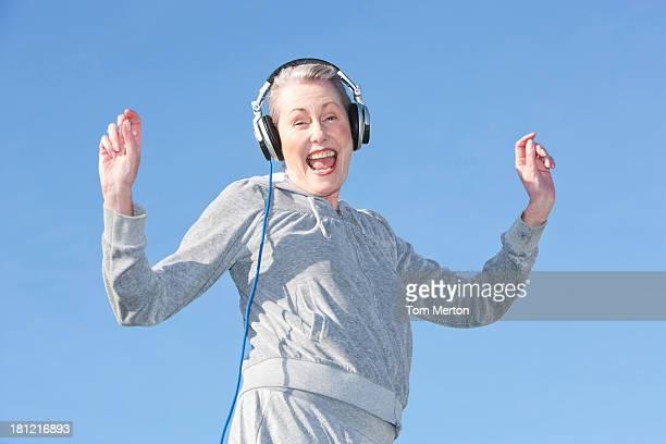senior mujer baile y música a través de auriculares