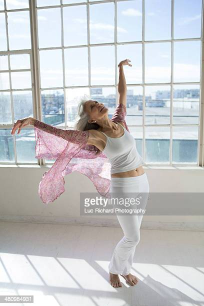 Senior woman dancing in sunlit apartment