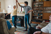 Senior woman is dancing in the living room with her teenage grandson.