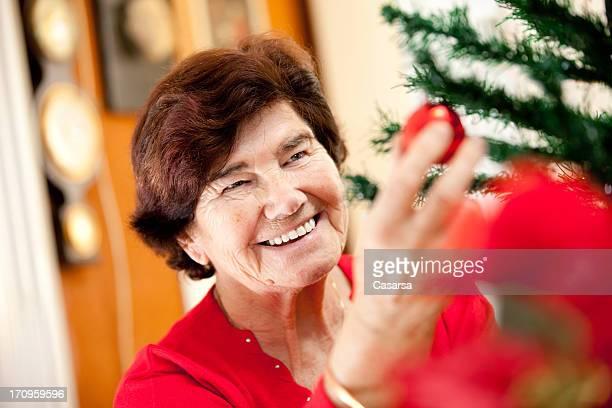Senior Frau dekorieren ein Weihnachtsbaum