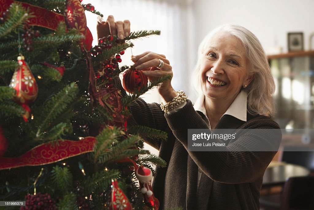 Senior woman decorating Christmas tree : Stock Photo