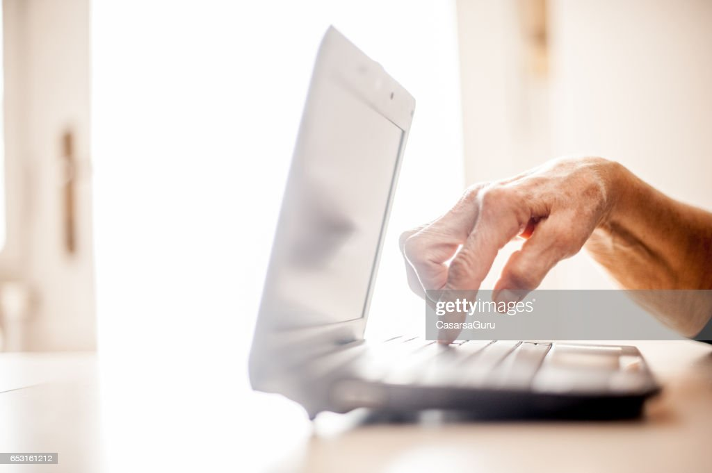 Senior Woman Determined To Use Computer - Close Up Hands : Photo