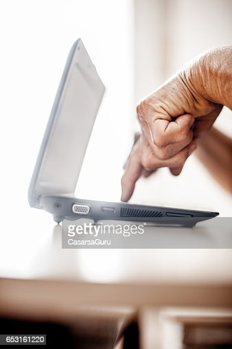 Senior Woman Determined To Use Computer - Close Up Hands : Stockfoto
