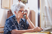 Senior woman dialing a number on her phone at home.