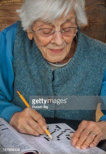 Senior woman doing a crossword puzzle : Stock Photo