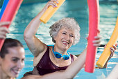 Smiling senior woman doing aqua fitness with swim noodles. Happy mature healthy woman taking fitness classes in aqua aerobics. Healthy old woman holding swim noodles in hand doing aqua gym with young